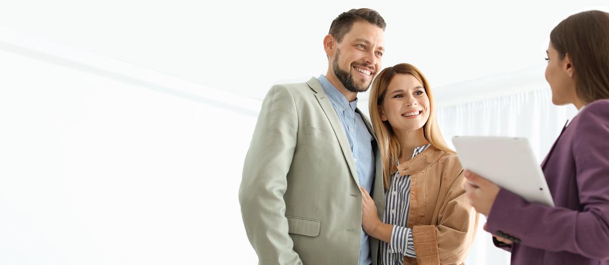 Frau hängt weiße Laken im Garten auf die Wäscheleine
