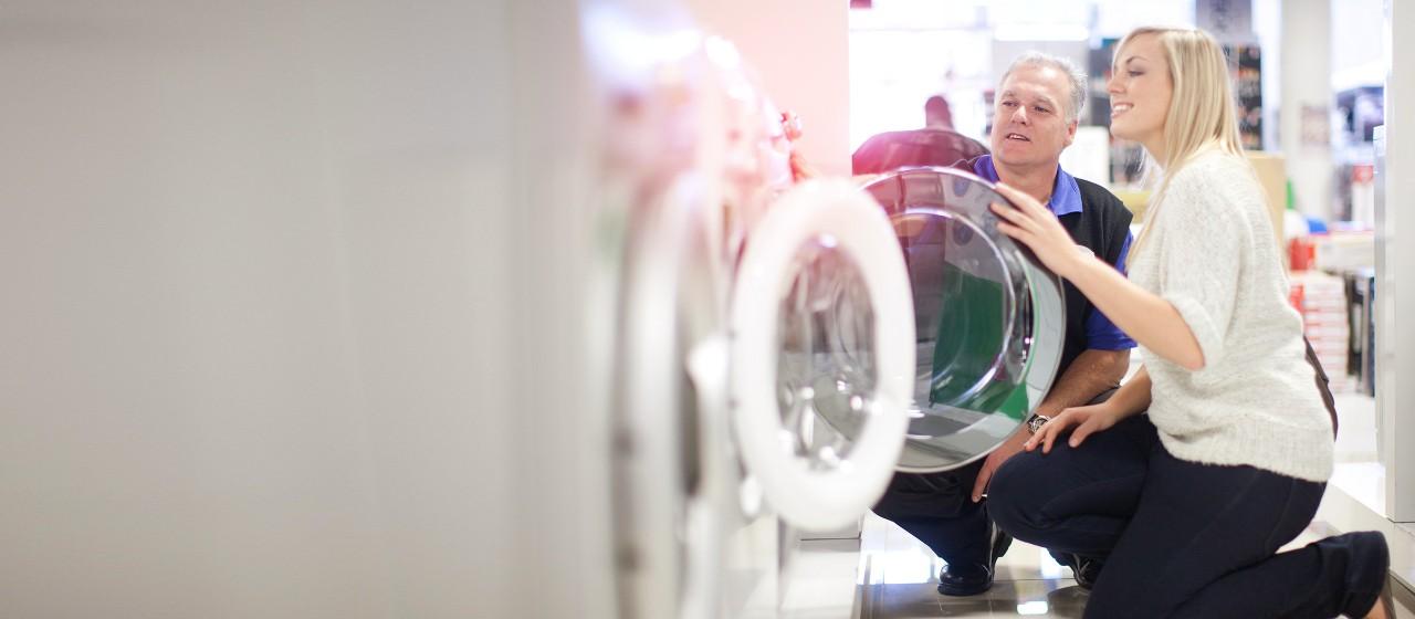 Ehepaar schaut sich eine Waschmaschine im Laden an