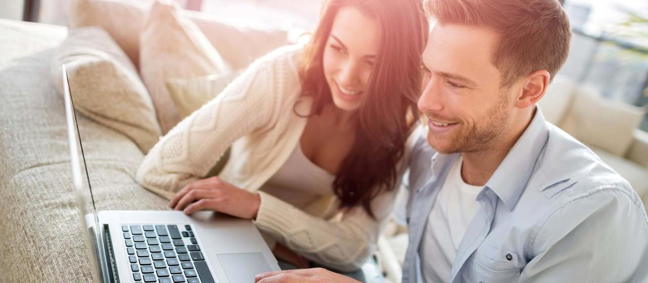 Mann und Frauen sitzen auf Couch und schauen gemeinsam in Laptop
