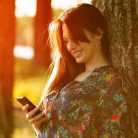 Frau lehnt sich an einen Baum mit Handy in der Hand
