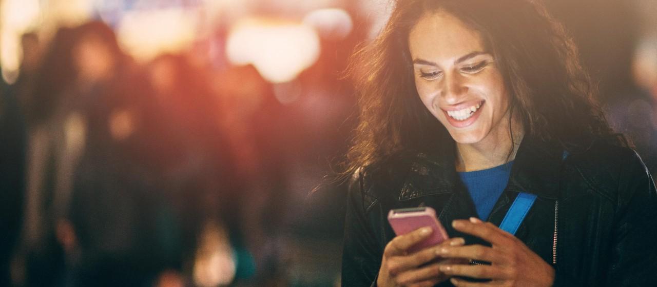 Junge Frau schaut gemeinsam mit einem Häschen ins Smartphone